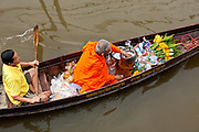 "10 JULY 2011 - AMPHAWA, SAMUT SONGKRAM, THAILAND:  A Buddhist monk from Wat Amphawan Chetiyaram in Amphawa, Thailand, about 90 minutes south of Bangkok, sorts the alms he has been presented with as he is paddled down the main canal during his alms round. Most of the monks from the temple use boats to go from house to house on their alms rounds. The Thai countryside south of Bangkok is crisscrossed with canals, some large enough to accommodate small commercial boats and small barges, some barely large enough for a small canoe. People who live near the canals use them for everything from domestic water to transportation and fishing. Some, like the canals in Amphawa and nearby Damnoensaduak (also spelled Damnoen Saduak) are also relatively famous for their ""floating markets"" where vendors set up their canoes and boats as floating shops.       PHOTO BY JACK KURTZ"