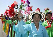 North Koreans wave flowers as South Koreans arrive at Sunahn airport in North Korea's capital Pyongyang August 14, 2003. /Lee Jae-Won