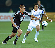DC United forward Adam Cristman (in black) races for the ball against Kansas City's Roger Espinoza. United defeated the wizards 2-1 to earn their first points of the season.