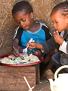 Elfnesh and Banga's son, Tariku Banga (left), tucks in to his lunch of cabbage and bread.