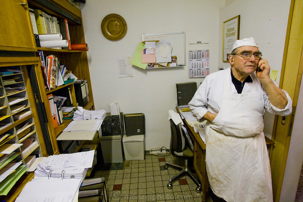 Marcus Dirr's father Peter Dirr, also a master butcher, speaks on the phone at his son Marcus Dirr's shop in Endingen, near Freiburg im Breisgau, Germany.  (Marcus Dirr is featured in the book What I Eat: Around the World in 80 Diets.)  MODEL RELEASED.