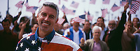 Portrait of happy mid-adult man with crowd celebrating Independence Day(USA)