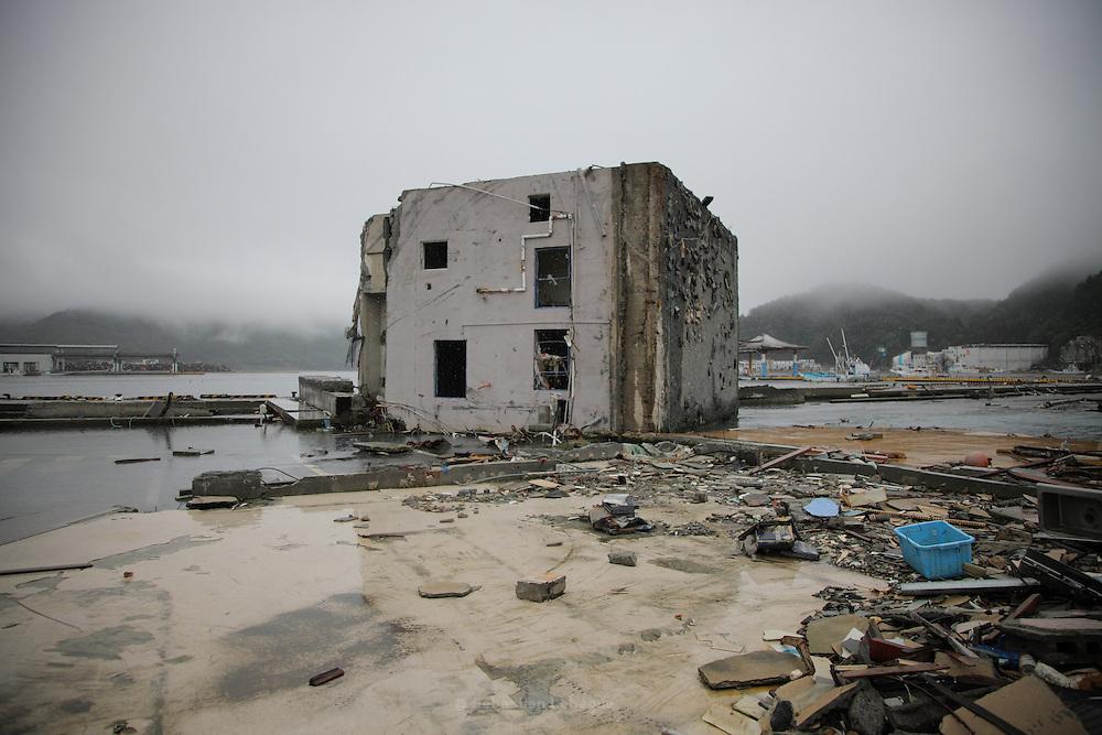 Onagawa - Béton - Juin 2011<br /> Au front de mer, un cube de béton de 6 mètres de côté, anciennement une habitation, fût simplement roulé comme un cailloux de rivière. Dans le garage, un véhicule tient toujours sa place en position couchée. Les lieux de vie s'exposent aux observateurs à l'horizontale.
