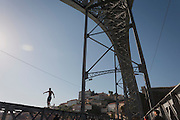 Silhouette of a young man about to dive off the Ponte de Dom Luis I (bridge) for tourist tips in Porto, Portugal. The Dom Luís I (or Luiz I) Bridge (Portuguese: Ponte Luís I or Luiz I) is a double-decked metal arch bridge that spans the Douro River between the cities of Porto and Vila Nova de Gaia in Portugal. At the time of construction its span of 172 m was the longest of its type in the world.