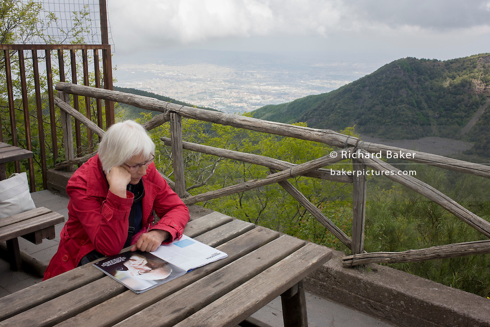 Lady reads magazine during visit to the Vesuvius volcano.