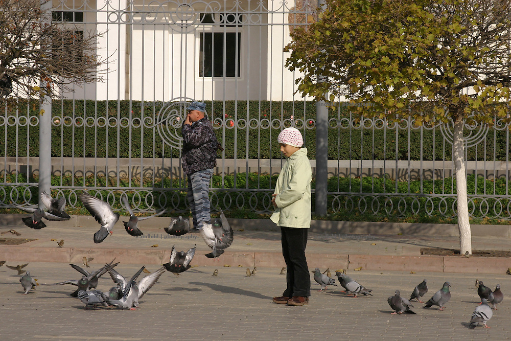 Ein Mädchen beobachtet Tauben vor dem bewachten Regierungsgebäude in Machatschkala, Dagestan. A girl watches the pigeon in front of the guarded government building in Makhachkala, Dagestan.