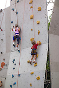 Surprisingly young children climb and rappel (abseil) while harnessed and roped on a practice wall in downtown Cortina d'Ampezzo, in the Dolomites mountains, Italy, Europe. The mountain town of Cortina d'Ampezzo (Ladin: Anpëz, German: Hayden, at 1224 meters/4016 feet elevation) is surrounded by the Dolomites (Dolomiti, a part of the Southern Limestone Alps) at the top of Valle del Boite in the Province of Belluno, Veneto region, Italy. This ski resort hosted the 1956 Winter Olympics. UNESCO honored the Dolomites as a natural World Heritage Site in 2009.