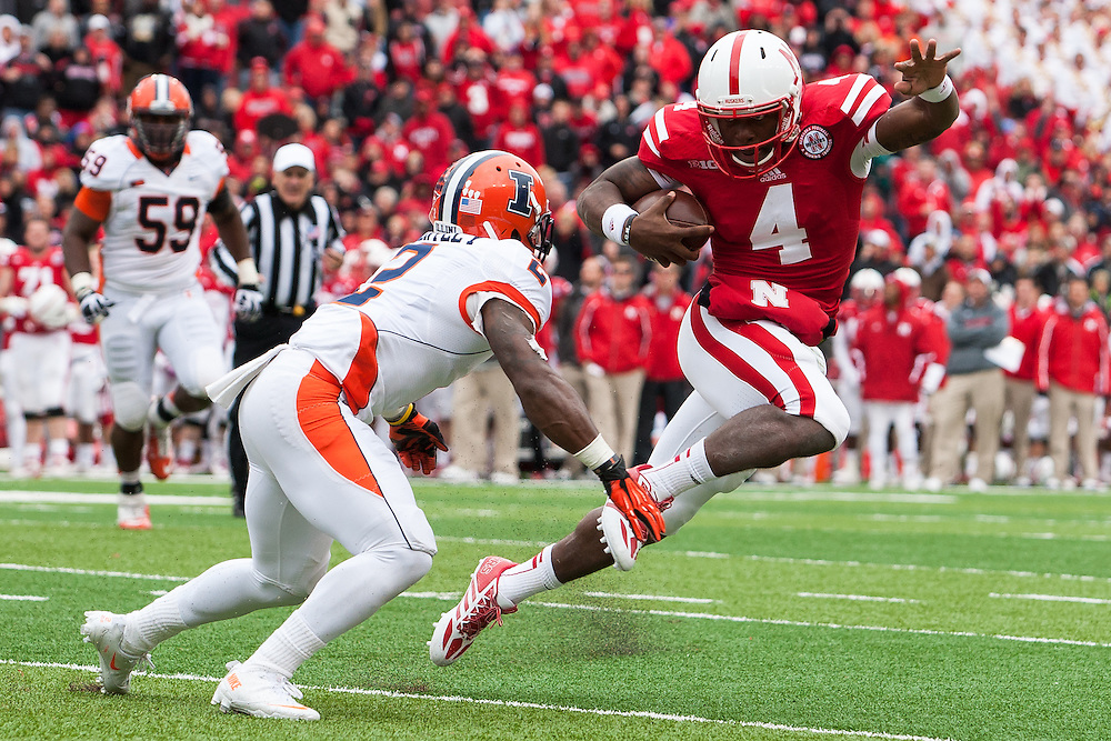 October 5, 2013: Quarterback Tommy Armstrong Jr. (4) of the Nebraska Cornhuskers tries to avoid defensive back V'Angelo Bentley (2) of the Illinois Fighting Illini at Memorial Stadium in Lincoln, Nebraska. Nebraska defeated Illinois 39 to 19.