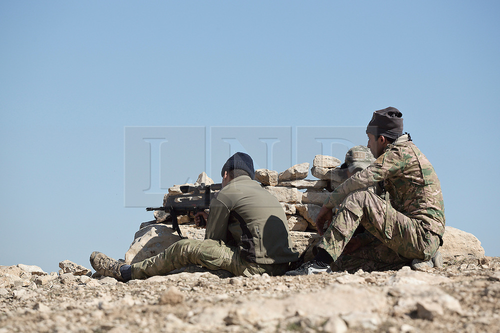Licensed to London News Pictures. 20/02/2017. Albu Saif, Iraq. Iraqi Emergency Response soldiers watch from a rocky outcrop for any ISIS movement as colleagues take a break during the assault of Albu Saif during the offensive to retake western Mosul from Islamic State militants.<br /> <br /> The settlement of Albu Saif is located on high ground overlooking Mosul Airport and as such is a strategic point that needs to be taken as part of the operation to retake the western side of Mosul. Photo credit: Matt Cetti-Roberts/LNP