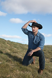 cowboy kneeling down on a grassy hillside