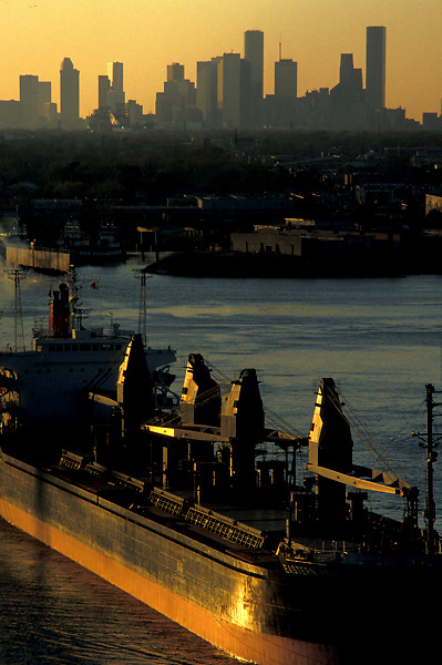 Tanker passing through the Port of Houston in front of the skyline at sunset