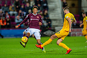 Jon Guthrie (#27) of Livingston FC clears the ball ahead of Sean Clare (#8) of Heart of Midlothian FC during the Ladbrokes Scottish Premiership match between Heart of Midlothian FC and Livingston FC at Tynecastle Park, Edinburgh, Scotland on 4 December 2019.