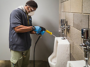 "19 MARCH 2020 - DES MOINES, IOWA:  DANIEL BROWN, a worker for Des Moines Public Schools, sanitizes and disinfects the urinals in a boys' bathroom at Central Campus, a high school in the Des Moines Public Schools system. Des Moines schools are closed for at least 30 days because of the coronavirus and officials are using the time to ""deep clean"" and sanitize each school. On Thursday morning, 19 March, Iowa reported 38 confirmed cases of the Coronavirus. Restaurants, bars, movie theaters, places that draw crowds are closed for at least 30 days. There are no ""shelter in place"" orders in effect anywhere in Iowa but people are being encouraged to practice ""social distancing"" and many businesses are requiring or encouraging employees to telecommute.      PHOTO BY JACK KURTZ"