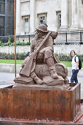 "© Licensed to London News Pictures. 25/07/2017. London UK. London, UK.  25 July 2017.  A sculpture called ""The Mud Soldier"", by the artist Damian Van Der Velden, a graduate of the Royal Academy of Arts of The Hague, is unveiled in Trafalgar Square.  Crafted with sand mixed with mud from Passchendaele, Flanders Fields, Belgium, this artwork will be displayed for four days to mark the centenary of Passchendaele and those who lost their lives in the Great War.  The artwork will slowly dissolve away as it is exposed to rain. Photo credit : Stephen Chung/LNP"