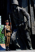 Soldier stands at attention with a rifle to guard the Warsaw Uprising Monument, Poland.