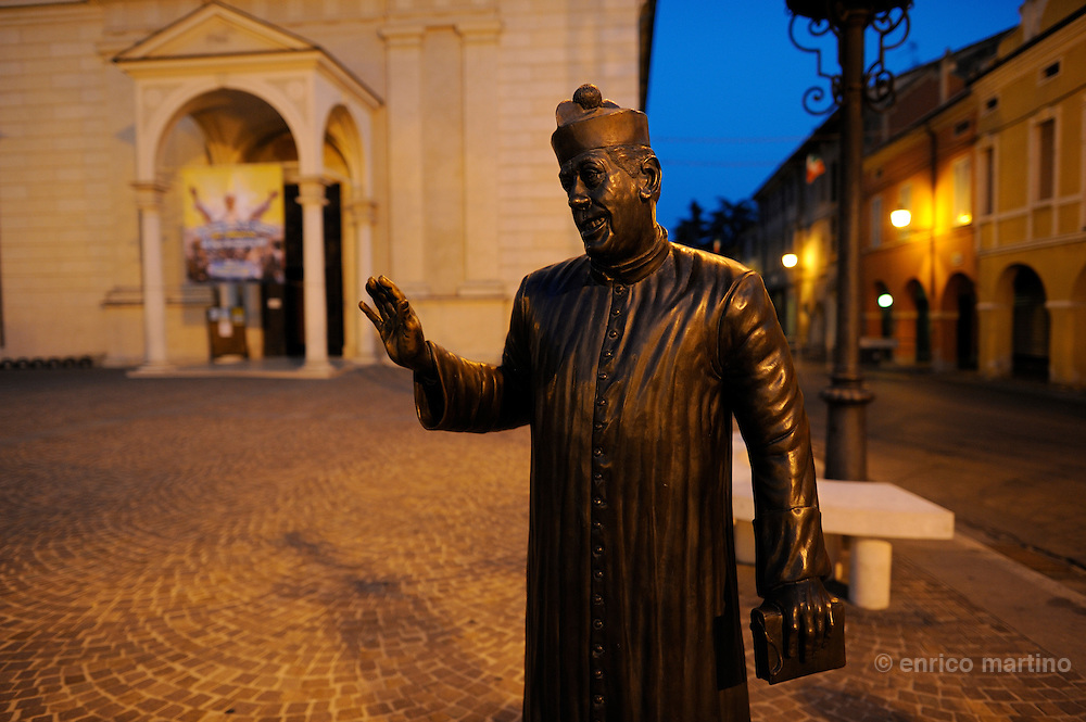 """Brescello, monument to don Camillo in front of """"his"""" church on the main square. Located near the Po river this town is famous for being the set for one of Italy's most loved film series: that of Peppone and Don Camillo, played by Gino Cervi and Fernandel and based on the books by Giovannino Guareschi."""