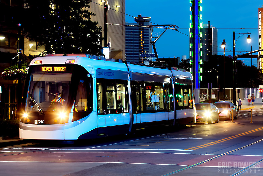 Streetcar in traffc in downtown Kansas City at dusk.