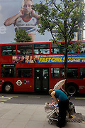 A mother feeds her baby near the inspiring image of Team GB gold medallist heptathlete Jessica Ennis which adorns the exterior of the Adidas store in central London's Oxford Street, during the London 2012 Olympic Games. The ad is for sports footwear brand Adidas and their 'Take The Stage' campaign which is viewable across Britain and to Britons who have been cheering these athletes who have been winning medals in numbers not seen for 100 years. Their heroic performances have surprised a host nation who until the victories, were largely anti-Olympics - now adoring their darling Ennis and her good looks.