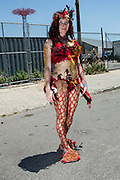 Brooklyn, NY - 18 June 2016. A woman wearing an elaborate, red mermaid costume poses before the parade.