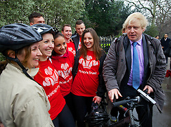 """Mayor of London Boris Johnson gets asked to pose impromptu with a group who were cycling on 'Boris bikes' all over London for charity and who came across the mayor as he was announcing he will create a """"Crossrail for the bike"""" as part of his plans to invest nearly £1 billion investment in London cycling, March 7, 2013. Photo by Andre Camara / i-Images."""