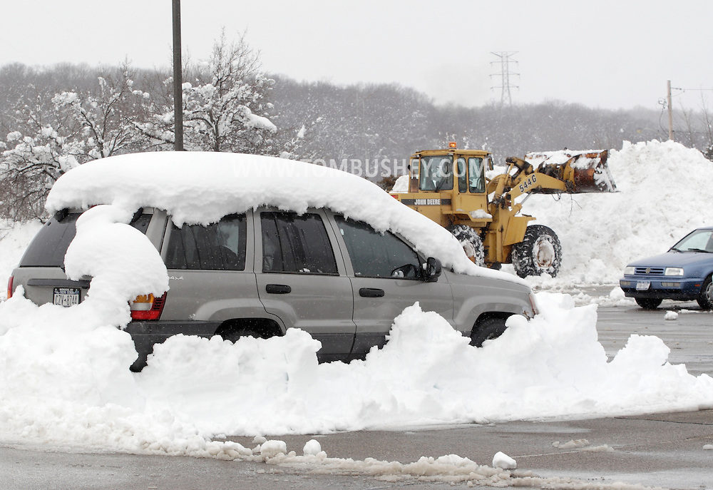 Monroe, New York - A vehicle  is covered in snow in a commuter parking lot the morning after a storm dropped 31 inches of snow and a plow cleared the lot around the vehicle. Feb. 27, 2010. A front-end loader is moving more snow from the parking lot in the background.