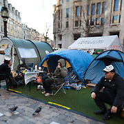Anonymous activists relaxing over coffees. Activists all over the world have taken on the mask, modelled on Guy Fawkes and the film character V in defiance of the establishment.   The camp Occupy London Stock Exchange outside St Paul's Cathedral was in the morning served with eviction notice after months of legal battle with the Corporation of London. The site was occupied Oct 15th.