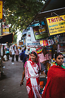 A woman walks along College Street in Kolkata, India.