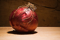 Studio still lifes of a red onion in front of a wood background.