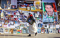 A rebel supporter holding a portrait of a relative killed in the fighting walks past a wall festooned with images of those killed