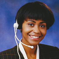 Portrait of a cheerful female telemarketing executive wearing headset.
