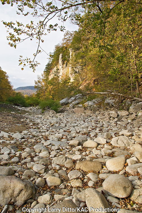 autumn colors along a dry river bed with limestone cliffs and rounded boulders in the river bed, Ozark Mountains near Boxley, Arkansas