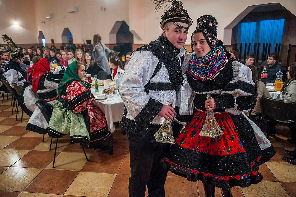A young couple from Tarsolt village who have just been married pose for a picture holding bottles of the local spirit which are shaped like the Eiffel Tower. These bottle have become a symbol of success in Romania. They are both working in the UK.