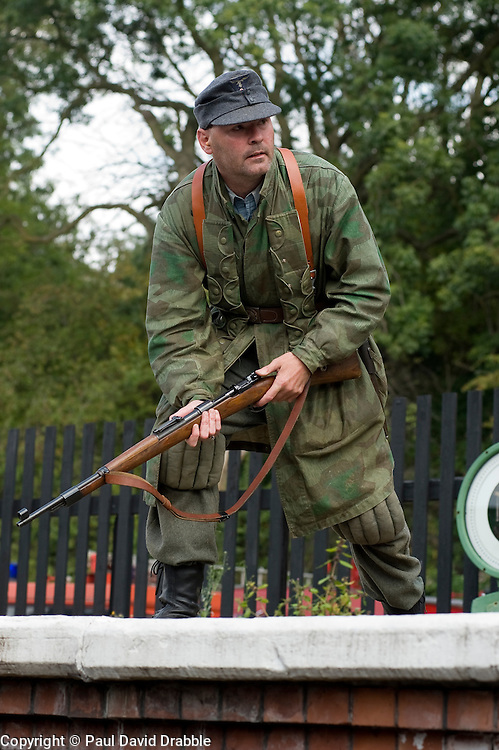 Reenactor from Northern World War Two Association, portraying a member of the 1st Fallschirmjaeger Division 'The Green Devils' prepares for a battle reenactment at Elsecar 1940s Weekend <br />