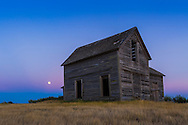 """The rising almost-Full Moon, a """"Blue Moon"""" of July 30, 2015, rising behind a rustic old farmhouse near Bow Island, Alberta. The Moon sits in the pibk Belt of Venus with the blue shadow of the Earth below. This is a single frame from a 600-frame time-lapse sequence, taken with the Canon 6D and 16-35mm lens."""