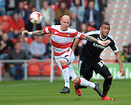 Richard Chaplow of Doncaster Rovers beats Reece Wabara of Barnsley to the ball during the Sky Bet League 1 match at the Keepmoat Stadium, Doncaster<br /> Picture by Graham Crowther/Focus Images Ltd +44 7763 140036<br /> 03/10/2015