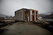 Au front de mer, un cube de béton de 6 mètres de côté, anciennement une habitation, fût simplement roulé comme un cailloux de rivière. Dans le garage, un véhicule tient toujours sa place en position couchée. Les lieux de vie sexposent aux observateurs à lhorizontale.