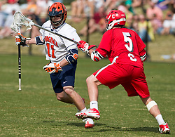 Virginia Cavaliers M George Huguely (11) is challenged by Cornell Big Red LSM/D Pierce Derkac (5).  The #1 ranked Virginia Cavaliers defeated the #4 ranked Cornell Big Red 14-10 at Klockner Stadium on the Grounds of the University of Virginia in Charlottesville, VA on March 8, 2009.