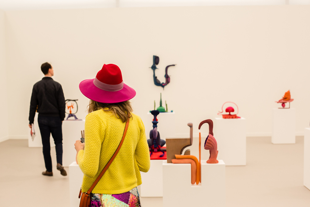 New York, NY - May 3, 2019. A woman in a bright hat and yellow jacket in the midst of Matthew Ronay's sculptures in the Casey Kaplan Gallery at the Frieze Art Fair on New York City's Randalls Island.