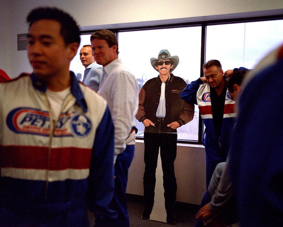 Richard Petty, NASCAR driver #1, Buena Vista, Florida, 2005.In likeness and thickness both, Richard Petty-the-man resembles nothing so much as Richard Petty-the-cardboard-cutout. A cardboard cut-out of NASCAR champion Richard Petty stands ignored by the men suiting themselves up into driving smocks in preparation for NASCAR driving school at the Richard Petty Driving Experience in Walt Disney World's The Magic Kingdom.  Fans of racing can ride-along a racetrak with a driver or choose to enroll in the school and race their own car around the track..Photo by Susana Raab