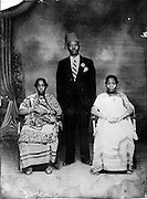 A Nubian elder has his photograph taken with his wives.  (1940s)