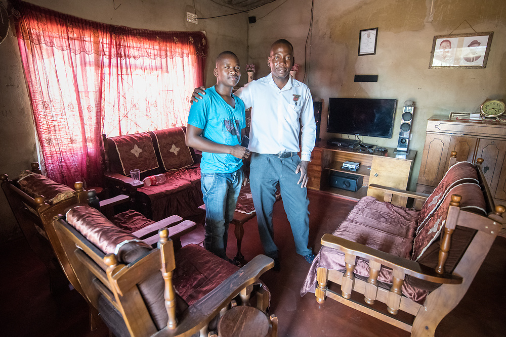 A father and son stand together inside their home in Botswana. Chobe National Park - Botswana