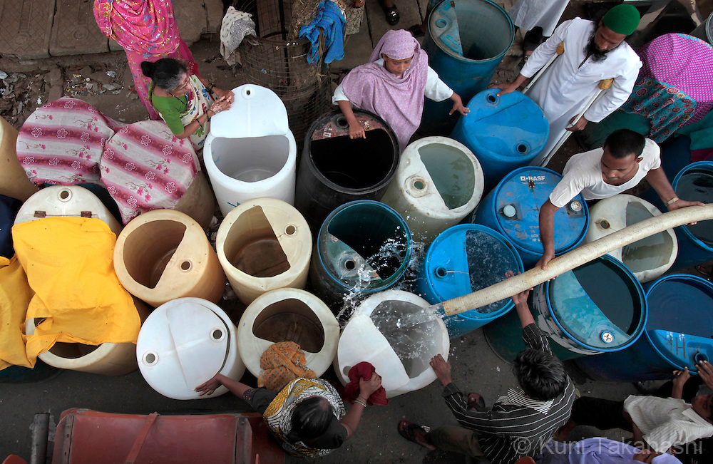 Residents of Shivaji Nagar neighborhood in Mumbai, India get water from water tanker on March 23, 2010. Due to the lack of rain in the monsoon season, Mumbai faced one of the worst water shortages in its history and the city government was forced to cut 15 % of its water supply. <br />