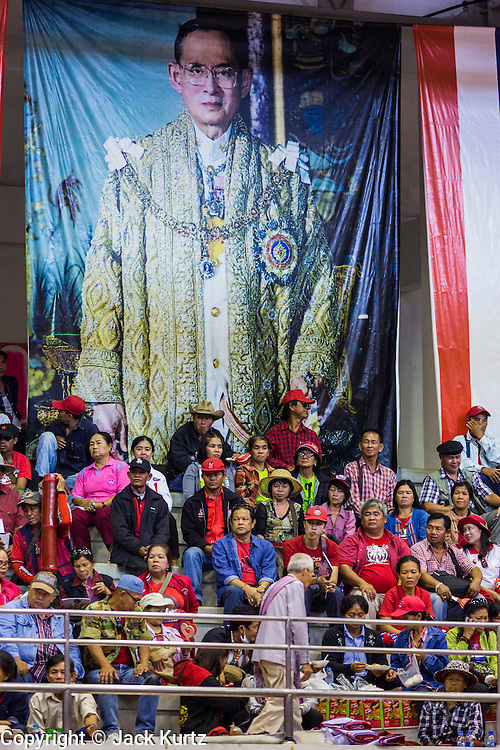 """23 FEBRUARY 2014 - NAKHON RATCHASIMA (KORAT), NAKHON RATCHASIMA, THAILAND: Thai Red Shirts sit under a portrait of Bhumibol Adulyadej, the King of Thailand, at the Red Shirt meeting in Korat. The United front of Democracy against Dictator (UDD or Red Shirts), which supports the elected government of Yingluck Shinawatra, staged the """"UDD's Sounding of the Battle Drums"""" rally in Nakhon Ratchasima (Korat) to counter the anti-government protests that have gripped Bangkok since November. Around 4,000 of UDD's regional and provincial coordinators along with the organization's core members met at Liptapunlop Hall inside His Majesty the King's 80th Birthday Anniversary Sports Complex in Korat to discuss the organization's objectives and tactics against anti-government protestors, which the UDD says """"seek to destroy the country's democracy."""" The UDD leadersa announced that they will march to Bangkok and demonstrate against anti-government protests led by Suthep Thaugsuban.   PHOTO BY JACK KURTZ"""