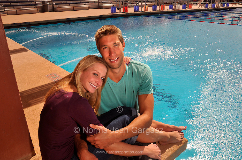 "Matt Grevers, (right), and Annie Chandler are U.S. National Swim Team members who train together at the University of Arizona.  They got engaged on February 11 after a race at a swim meet in Columbia, Missouri.  Matt won first place in backstroke.  When Annie presented the awards, Matt got down on one knee on the podium and proposed.  Annie said, ""Yes."""