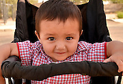 South Tucson resident, Jose Evan Esais, 1, enjoys an early Sunday morning stroll with his mother in the southside community, Tucson, Arizona, USA.