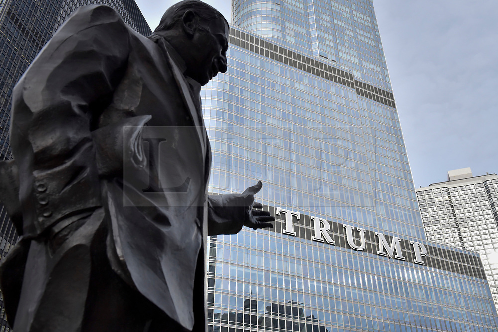 "© Licensed to London News Pictures. 21/12/2017. CHICAGO, USA.  A statue of American newspaper columnist Irv Kupcinet appears to point at the sign adorning the exterior of Trump International Hotel and Tower in downtown Chicago displaying the word ""TRUMP"" in 20 foot high letters.  The United Nations has just voted to reject US President Donald Trump's recognition of Jerusalem as capital of Israel.  Photo credit: Stephen Chung/LNP"