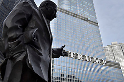 """© Licensed to London News Pictures. 21/12/2017. CHICAGO, USA.  A statue of American newspaper columnist Irv Kupcinet appears to point at the sign adorning the exterior of Trump International Hotel and Tower in downtown Chicago displaying the word """"TRUMP"""" in 20 foot high letters.  The United Nations has just voted to reject US President Donald Trump's recognition of Jerusalem as capital of Israel.  Photo credit: Stephen Chung/LNP"""