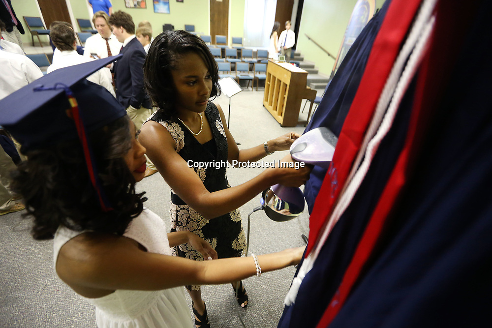 TCPS graduates Deadra Ruffin and Arielle Rogers work to steam the wrinlkes out of Ruffin's graduation gown as they get ready for the graduation ceremony that was held at West Jackson Street Baptist Church on Saturday.