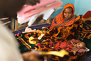 A woman sits with her malnourished child at the UNICEF-sponsored Mao therapeutic feeding center in the town of Mao, Kanem region, Chad on Monday February 13, 2012.