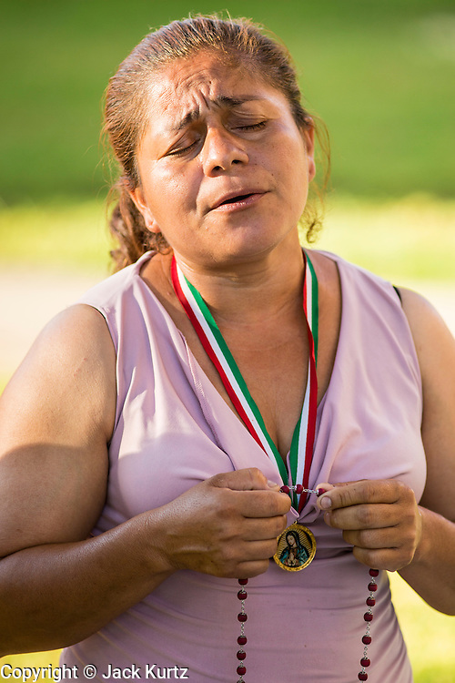 18 JUNE 2012 - PHOENIX, AZ: GEORGINA SANCHEZ, prays that the US Supreme Court will overturn Arizona's anti-immigrant law Monday. About 20 people, members of the immigrant rights' group Promise AZ (PAZ) held a prayer vigil at the Arizona State Capitol in Phoenix Monday praying that the US Supreme Court would overturn SB 1070, Arizona's controversial anti-immigrant law. The court's ruling had been expected Monday, June 18 but the the court said the ruling would not come out until later this month. Members of PAZ said they would continue their vigil until the ruling was issued.     PHOTO BY JACK KURTZ